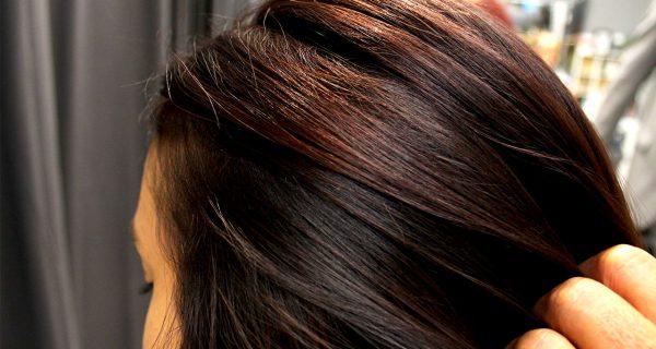 hair stylist running hands through shiny hair