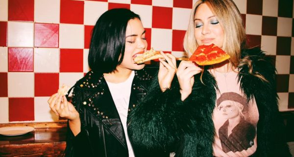 2 girls eating pizza in retro diner