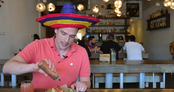 man with sombrero eating tacos